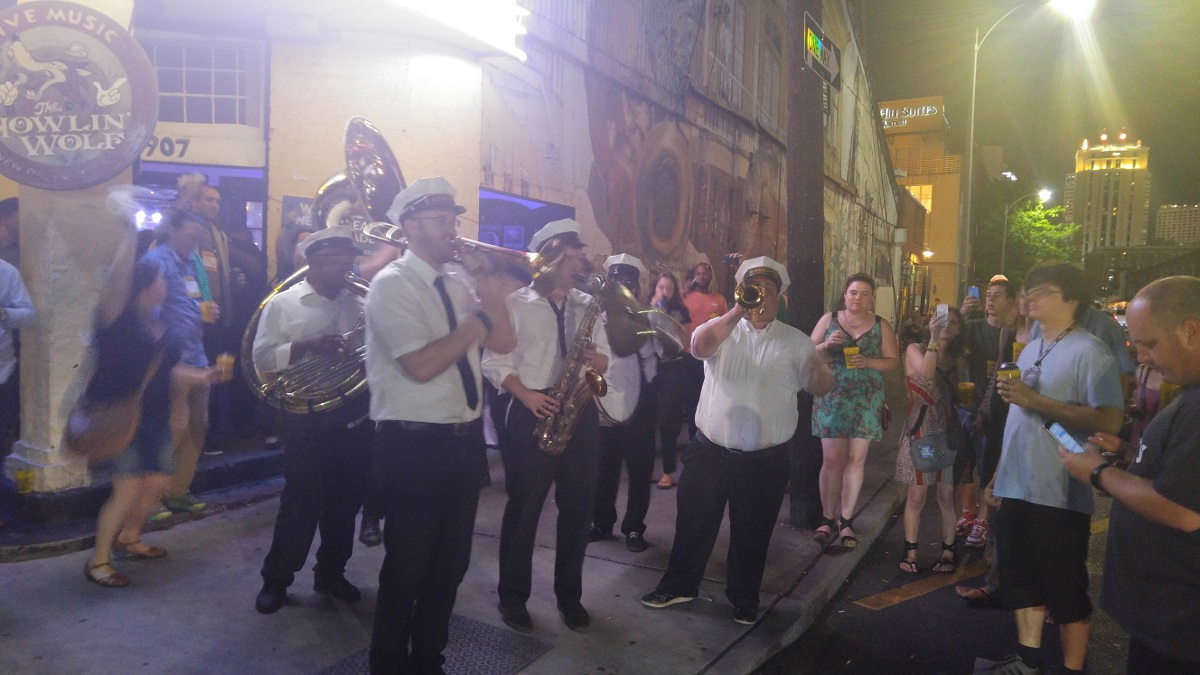 Brass Band on New Orleans street surrounded by crowd taking photos